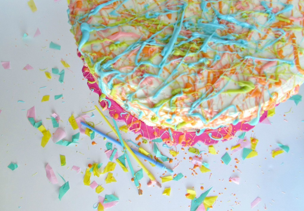 splatter paint cake with orange, blue, green and pink