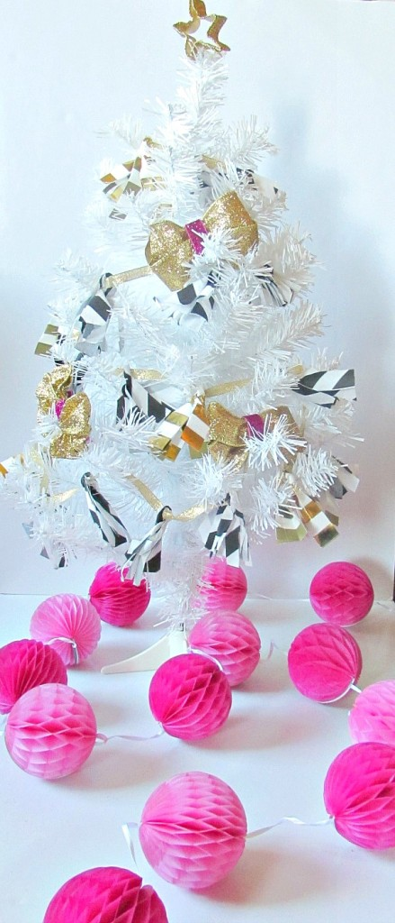Shiny gold, pink and black decor on white Christmas tree